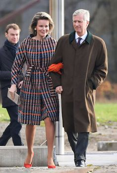Queen Mathilde of Belgium wraps up in a very vibrant checked belted Natan coat teamed with a pair of bright orange leather gloves, a matching kitten heels and a putty-colored clutch bag. Meanwhile King Philippe of Belgium, looked smart in a white shirt, tie and practical green overcoat, as they carried out a busy day of engagements in Belgium.