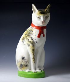 Large scale Staffordshire pottery figure of a seated cat with a knowing smile  circa 1835