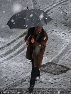 A man crosses a street as snow falls over Rome on February 3 2012