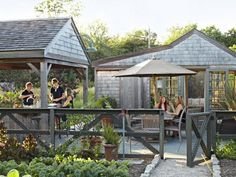 The owner of this Rhode Island home enlisted a contractor to build an open-air kitchen and an enclosed living room—both outfitted with electricity and water—alongside his vegetable garden.