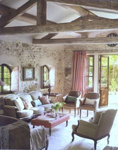 Great room with old stone walls, exposed ceiling rafters, antique doors.