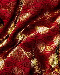 African Brocade fabric a shimmery wine red color with gold designs