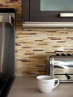 Translucent Tile  Consisting of slender glass tile in creamy hues and stone tiles in coppery shades, the radiant translucence of this mosaic backsplash adds depth to the kitchen. A neutral color palette such as this one can warm up a sleek, contemporary space. The trendy narrow tiles maintain a modern vibe.