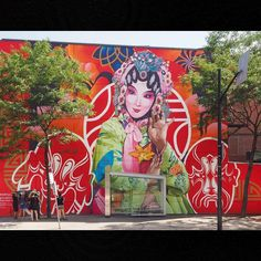 """Bryan Beyung in Chinatown, Montreal """"Chinatown 2015, #Beyung #Pendon #mumtl. Painted on a bright red background (synonymous with prosperity and bravery in the Chinese culture), the image the image features a female Chinese opera singer decorated with a yellow, blooming lily (fleur de lys) in the foreground. In the background, a circle represents unity while the masks on either side signify the characteristic mix of optimism (left mask) and nostalgia (right mask) upon arrival in a new…"""