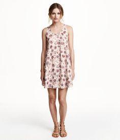 Flared, sleeveless dress in woven fabric with a printed pattern. Opening at back of neck with button. Unlined.