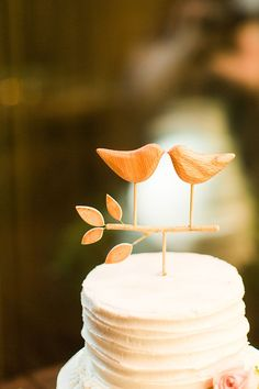A simple wood lovebird cake topper on a buttercream wedding cake for a rustic wedding.