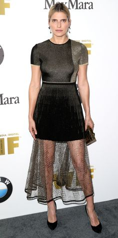 Lake Bell in a shimmery gold-embroidered black knit dress with a pleated mini, paired with drop earrings, an embellished box clutch, and black suede pumps rounded out her look.