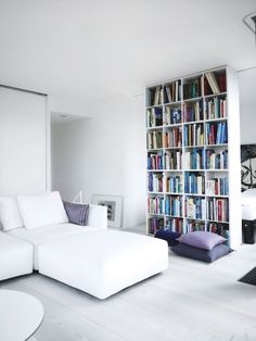 Floor to ceiling bookshelf stuffed with books dividing a small, white room with purple pillows in two #Decoração #decoration #ornamentos #composição #detalhes #details #decor #adornment #ornament l #Casa #lar #home #house # maison