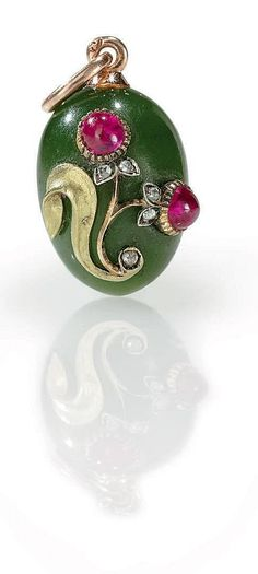 A Jeweled Gold-Mounted Nephrite Egg Pendant By Fabergé, with indistinct workmaster's initials, probably for Michael Perchin, St. Petersburg, 1896-1903 Ovoid, the hardstone body applied with a gold leaf and a flower set with two cabochon rubies and rose-cut diamonds, with gold suspension loop, marked on suspension loop