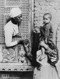 An Egyptian man leans through a small ornate window to hold his wife's hand.