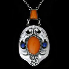 THEODOR FAHRNER   A rare silver pendant set with amber and lapis. German c.1900. Marks: 'TF' '935' 'DEPOSE'.  Size: Length of pendant 5 cm. Width 3.8 cm. Length with central amber 6.8 cm.  Lit.: Theodor Fahrner Jewelry