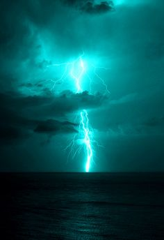 Lightning coursing from the heavens to the sea, with shades of blue and black embracing this streak of electrical current