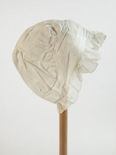 Cap - White muslin ribbed Helmet design, consisting of band gathered cord and full upper section . Frill around face. 1810 - 1820 (circa)