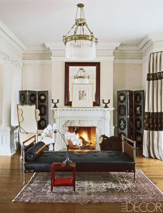 In the sitting room of a Jacobean Revival estate in Tuxedo Park, New York, designer Ernest de la Torre flanked the fireplace with a pair of Chinese lacquered screens. The mirror and side table are by Karl Springer, the daybed is by Jacques Adnet, and the Louis XIII chair was purchased at auction. The light fixture is antique, and the walls are covered in a Ralph Lauren Home wallpaper. Tour the home here.