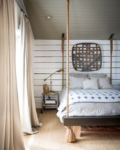 In the guest bedroom, a novel rope bed anchors the spacethe space. Accented with a blue-and-white swiss cross blanket, a seagrass rug, and a hanging tobacco basket, the room is full-on country without feeling too theme-y.
