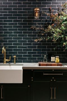 Black industrial luxe kitchen with black subway tiles and brass hardware