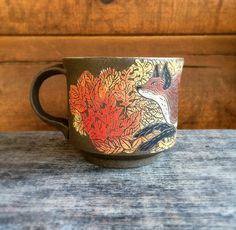 This chocolate brown mug is perfect for coffee, tea, or your choice beverage. The image is hand painted and carved using a ceramic technique called sgrafitto. No two mugs are alike, each are their own individual, unique piece of artwork.  This chocolate brown mug depicts a fox with autumn leaves. Stoneware and glazes are fired to cone 6.  Approximately 3 wide, 4 tall and will hold 10-12 ounces.  Silver Run Ceramics are dishwasher and microwave safe.