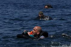 A Syrian refugee holding a baby in a lifetube swims towards the shore after their dinghy deflated some 100m away before reaching the Greek island of Lesbos, September 13, 2015. Of the record total of 432,761 refugees and migrants making the perilous journey across the Mediterranean to Europe so far this year, an estimated 309,000 people had arrived by sea in Greece, the International Organization for Migration (IMO) said. About half of those crossing the Mediterranean are Syrians fleeing…