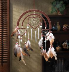 DREAMCATCHER HEART WINDCHIMES Feathers, beads and faux leather trim add authentic Southwestern styling to this one-of-a-kind windchime! Hang this triple-heart decoration where its sure to be admired by all. Los Dreamcatchers, Beautiful Dream Catchers, Dream Catcher Craft, Dream Catcher Native American, Felt Cover, Heart Decorations, String Art, Wind Chimes, Diy And Crafts