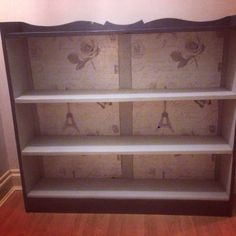 Upcycled and repaired vintage pine bookcase. Painted in slate grey and silver mist. Beautifully finished off with a Parisian theme wallpapered backing. Work done by Myself.