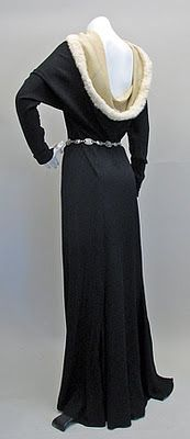 1930s black crepe with long, long scrunched sleeves, a figure defining skirt on the bias, and a grand deep ivory cowl neckline edged in white rabbit fur. There's a  hint of a medieval chatelaine to the style, yes?