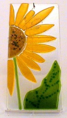 "Fused Glass Suncatcher Sunflower By Fenton Art Glass International . $20.00. This awesome sun catcher would look great hanging in any window of your house. It is sure to brighten up even the worst days. The ""Sunflower"" sun catcher is 6 3/4"" long and 3 1/8"" wide. It also comes with a wire on the top. (Suction cup or acrylic stand is not included). Made by Fenton International"