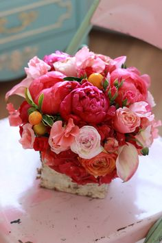 Flowers by Sachi Rose. Arrangement includes coral peonies, peach garden roses, kumquats, ranunculus, and sweet peas in a birch bark vase.