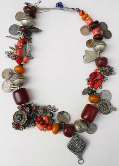 Berber necklace with coral beads, resin amber beads, some glass beads, little shells, silver coins, silver and metal beads and objects. It's approx. 70 years old.  One string with three short pieces of 3 strings between.   450 Euro