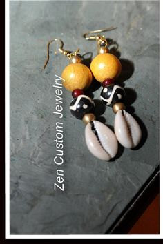 African inspired earrings with large Nangka wood beads, brass beads , mud-cloth bead and the prosperous cowrie shell. $18.00