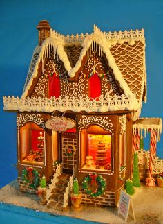 "Gingerbread house is approx. 15"" tall and 13"" wide. Baked goods, signs, and planters are made from gumpaste. Wrought iron is made ..."