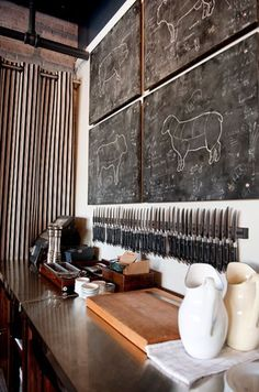 .This is simple and very cool -- 4 boards painted with blackboard paint (butcher drawing by an artistic friend), quite a few magnetic knife strips, lots of black handled knives.  black and cream curtain and old fashioned looking counters.
