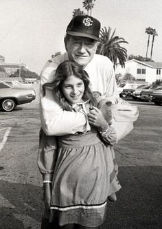 Duke, only a month shy of his 70th birthday, demonstrates his affection for youngest child Marisa Wayne outside a USC celebrity baseball game in Los Angeles on April 17, 1977.