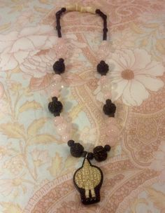 Romantic necklace with white coral, hindu prayer beads, rose quartz round beads, dark wood beads, hand carved many arms buddah pendant.