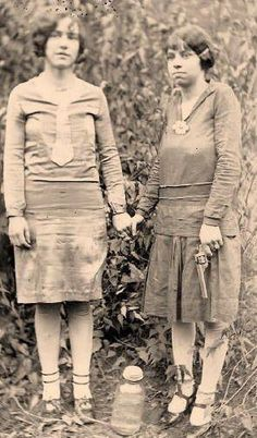 Women pose with their moonshine and a revolver in the woods of West Virginia.