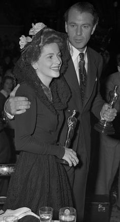 Joan Fontaine and Gary Cooper holding their Oscars at the Academy Awards after-party, 1942.