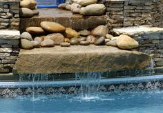 A view of the above waterfall, showing the multiple tiers and the layered stones on either side. The water is recycled from a reservoir beyond the top tier.