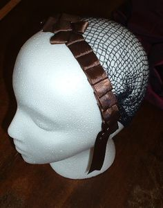 Hairnet (not snood) of ribbon.  The hair is pinned up first, and then the net is put on.