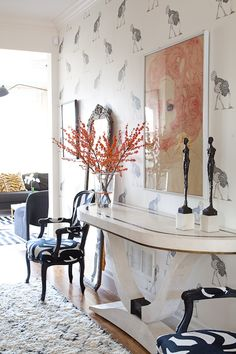 Black & white hallway with layered prints and pops of color; electic entry accent wall
