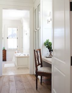 A cream-coloured ensuite opens off the principal bedroom.      Wide floorboards in a pale wood are a lovely contrast to the principal bathroom's glossy white floor tiles. A glass-fronted, floor-to-ceiling armoire offers storage and complements the fresh and airy feel of the space.