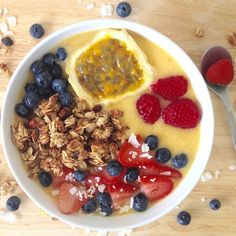 Banana Mango smoothie bowl blended with coconut water, topped with homemade granola, berries, and passion fruit