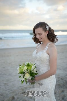 Beach bride with beautiful wedding dress and and green bouquet of flowers in Ocean City, MD: https://www.roxbeachweddings.com/