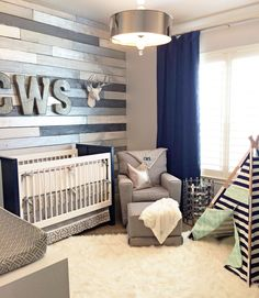 A metallic wood wall nursery with gray, white and navy as an accent color. Gorgeous room!