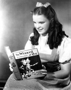 Judy Garland, dressed in her Wizard of Oz costume and reading the Wizard of Oz.