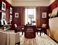 In a New York City apartment, the study is appointed with a desk and straw-marquetry cabinet, both by Ernest de la Torre, a lamp (at center) commissioned from Mira Nakashima, and vintage André Sornay chairs covered in a Rose Tarlow Melrose House leather; the throw is by Ralph Lauren Home, and the rug is by Stark.