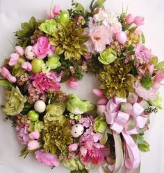 """This beautiful Easter flower door wreath sets on a grapevine wreath base.  The wreath is embellished with  greenery, beautiful pink roses, spring pink/white Hydrangea, pink/magenta peony , lime green roses, and apple green mums. The wreath is accented with four green/pink polka dots Easter eggs, and one pink , one white Easter eggs . finish the wreath with a cute green bird in the middle and pink and light green ribbon bow.     The wreath measures from tip to tip at 26"""" (L) x 26"""" (W) x…"""