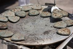 "Blue corn tlayacos in Puebla, Mexico. ""Tlacoyos are small, flattened masa pockets that are stuffed with either beans, cheese or fava beans and then grilled on a comal."""