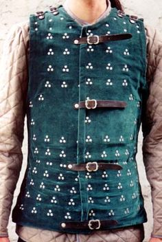 Medieval Armour - a brigandine. Small metal plates riveted to the fabric. Worn also over mail. Less expensive than plate or mail - everyone could do themselves