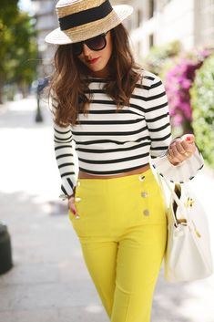 Striped crop top with yellow high wasted pants  Fashion Note: For some reason I think there should be a small monkey with a little hat that matches hers running around with this woman.