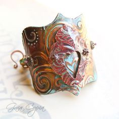 Embossed Copper Wonder Woman cuff with double heart and wire work on the inside. Gorgeous clasp. Embossed and painted leather on the inside. Hand made by Gaia Copia.