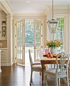 ♥ the rustic table paired with these chairs in a sweet blue..love those doors and all the crown molding
